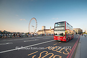 A red London bus driving over Westminster Bridge in London, England.
