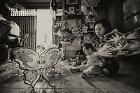 The women in Vietnam are really very hardworking. They multi-task very well looking after their young ones and making lanterns.