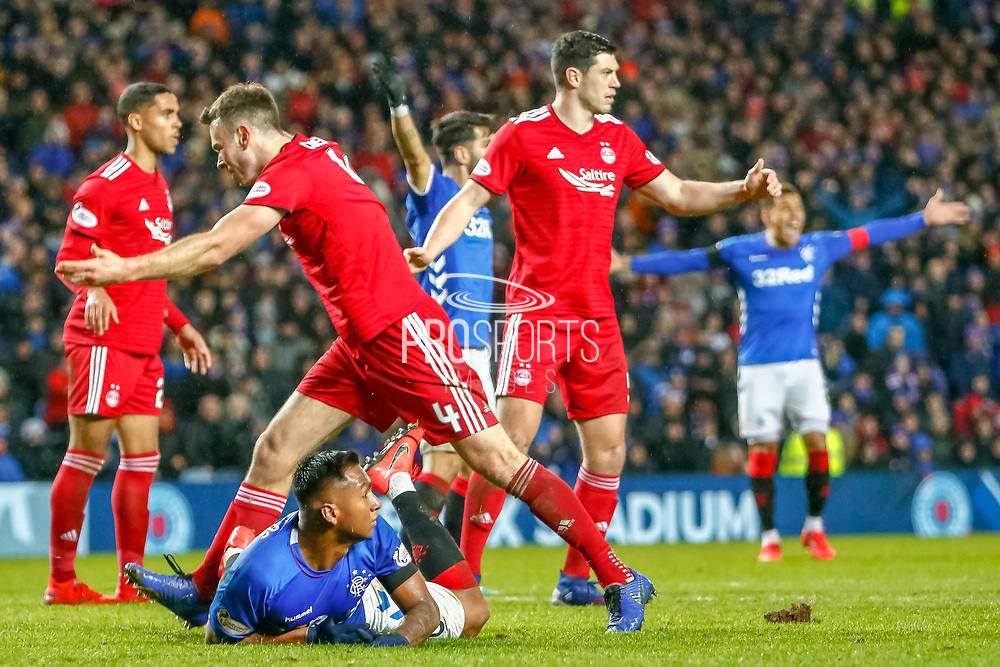 Alfredo Morelos goes down in the box and looks to the referee for a penalty during the William Hill Scottish Cup quarter final replay match between Rangers and Aberdeen at Ibrox, Glasgow, Scotland on 12 March 2019.