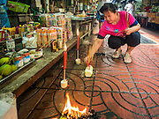 """17 AUGUST 2016 - BANGKOK, THAILAND:  A woman sets up the banquet for the spirits in front of her home during the Ghost Festival in the Chinatown section of Bangkok. The Ghost Festival is a Buddhist and Taoist holy day celebrated on the 15th day of the 7th lunar month. It is primarily celebrated in China and Chinese communities beyond China. In Thailand, it's celebrated in Thai-Chinese communities in Bangkok, Phuket and Chiang Mai.  On that day ghosts and spirits, including those of the deceased ancestors, come out from the lower realm to visit the living. Families prepare elaborate banquets for the spirits and burn """"ghost money"""" for the spirits to use in the other realm. It is a day for venerating dead relatives.     PHOTO BY JACK KURTZ"""