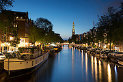 Typical Amsterdam canal scene - Westerkerk church, canal and barges along Prinsengracht in Amsterdam, Holland