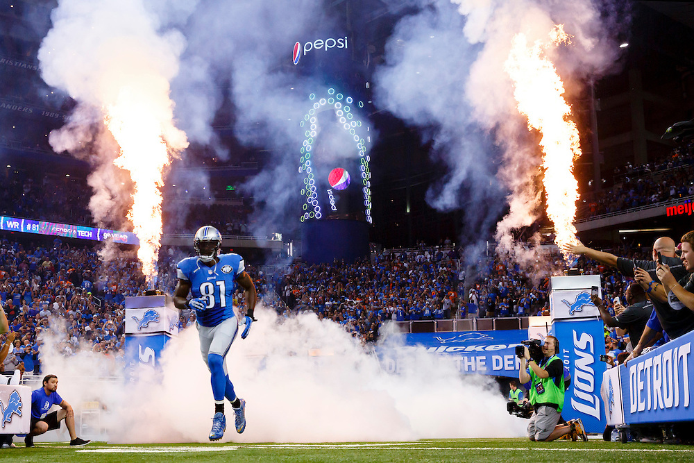 Detroit Lions wide receiver Calvin Johnson (81) runs out during player introductions for the Lions' NFL football game against the Denver Broncos, Sunday, Sept. 27, 2015, in Detroit. (AP Photo/Rick Osentoski)