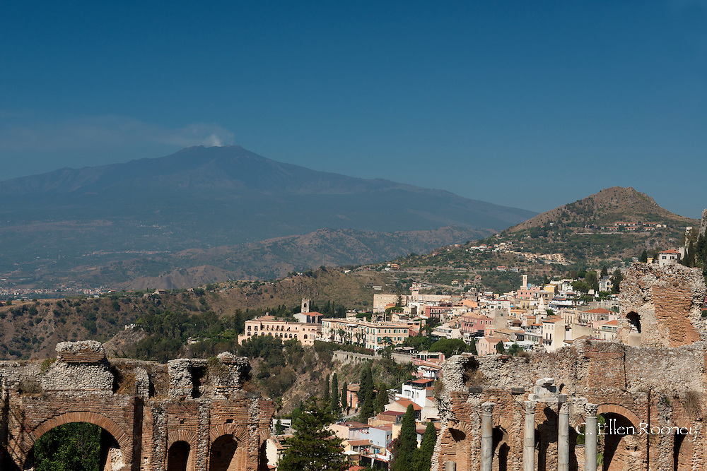 A view of smoke rising from Mt Etna, the Greek Theatre and  the town ofTaormina in Sicily, Italy