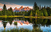 Sunrise lights on the Grand Tetons mountain ridge. Schwabacher's Landing, Grand Tetons National Park, Wyoming.
