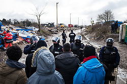 Licensed to London News Pictures. 03/03/2016. Calais, France. A group of refugees watch on as contractors tear down makeshift shelters. French authorities are clearing the southern half of the Calais 'Jungle' camp, which charities estimate to contain 3,500 people. Photo credit : Rob Pinney/LNP