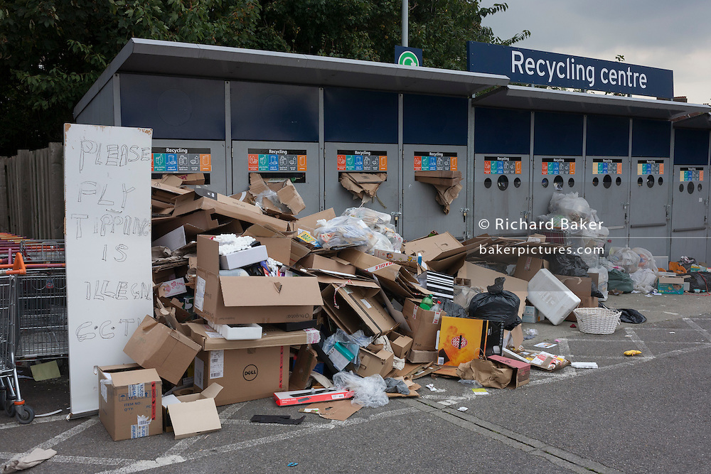 Despite a warning of CCTV, piles of fly-tipped cardboard have been dumped in a private Sainsbury's car park and recycling centre, on 19th September 2016, in Dulwich, south London. Sainsbury's here in Dulwich has a growing problem with fly-tipping rubbish despite security checks and CCTV present.