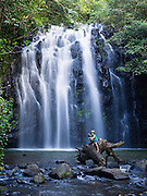 A boy sits on a long at the base of Ellinjaa Falls, in the Atherton Tablelands of Queensland, Australia.
