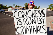 """July 6 - PHOENIX, AZ:  Frank Trejo, from Phoenix, pickets a street corner in Phoenix Tuesday morning to protest the federal budget deficit and Congressional inaction on immigration reform. Trejo pickets a different corner in central Phoenix every morning. He said he is not a member of the Tea Party, but that he is """"digusted"""" with both political parties and agrees with many of the Tea Party ideals.    Photo by Jack Kurtz"""