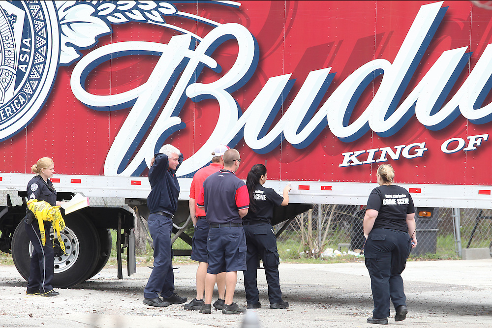 ANDREW KNAPP/STAFF -- March 18, 2013 -- North Charleston police officers examine a Budweiser truck after a delivery man was shot Monday afternoon outside the Neighbor Store at 1740 E. Montague Ave.