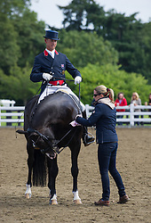 Olympic medal-winning equestrian Carl Hester is helped out by Gold Medal-winning team-mate Charlotte Dujardin at the British Dressage National Championships 2012, September 15th 2012. Photo by Nico Morgan/ i-Images.