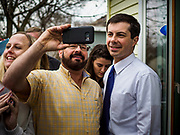 "17 APRIL 2019 - MARSHALLTOWN, IOWA:  Mayor PETE BUTTIGIEG poses for a selfie with a voter after a meet and greet at home in Marshalltown, Iowa. People came from as far away as Minneapolis, Minnesota and Rockford, Illinois to meet the mayor of South Bend, Indiana. ""Mayor Pete,"" as he goes by, declared his candidacy to be the Democratic nominee for the US Presidency on April 14. Buttigieg is touring Iowa this week. Iowa traditionally hosts the the first selection event of the presidential election cycle. The Iowa Caucuses will be on Feb. 3, 2020.           PHOTO BY JACK KURTZ"