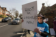 A campaigner asks motorists to hoot their horns as they pass Carnegie Library, in Herne Hill, south London on 2nd April 2016. The angry local community in the south London borough have occupied their important resource for learning and social hub for the weekend. After a long campaign by locals, Lambeth have gone ahead and closed the library's doors for the last time because they say, cuts to their budget mean millions must be saved. A gym will replace the working library and while some of the 20,000 books on shelves will remain, no librarians will be present to administer it. London borough's budget cuts mean four of its 10 libraries will either close, move or be run by volunteers. (Photo by Richard Baker / In Pictures via Getty Images).