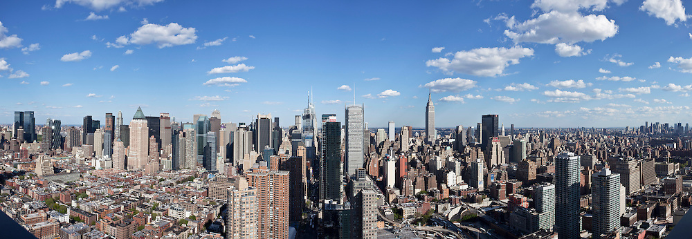 A panoramic photograph from the west side of Manhattan facing East.  Visible in the photograph are such famous buildings as Hearst Tower, The Bank of America Building, Empire State Building and the Financial District of Manhattan.