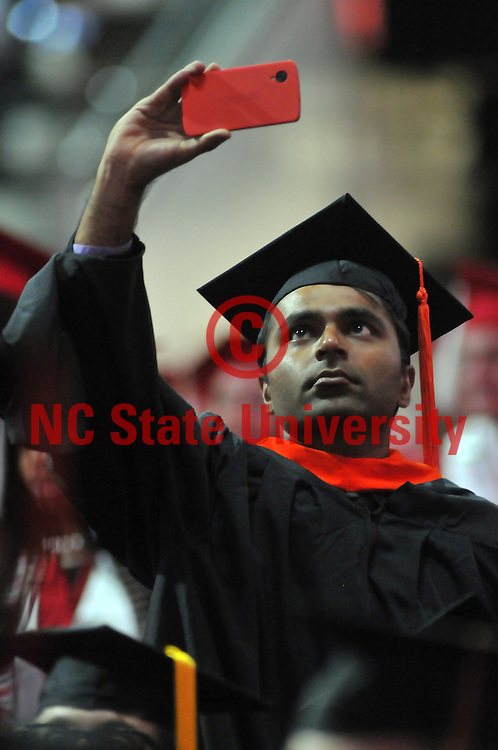 Graduate shoots a video from his seat upon entering PNC Arena for Commencement.