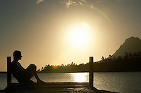 Man sitting on dock by lake side view.