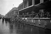 """17/03/1964<br /> 03/17/1964<br /> 17 March 1964<br /> St. Patrick's Day Parade, Dublin.  Thousands lined the streets of Dublin in blustery and wet weather to see the annual St. Patrick's Day parade organised by the National Agricultural and Industrial Development Association, which was the biggest ever. The Theme of the parade was """"Export"""". Picture shows the Minister of Justice, Mr Charles Haughey taking the salute at the G.P.O. at noon as the colour party which headed parade marched past the reviewing stand."""