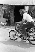 Magnus riding a moped. Glastonbury, Somerset, 1989