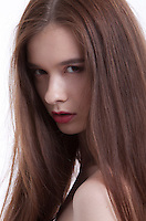 Portrait of beautiful young woman with long hair against white background