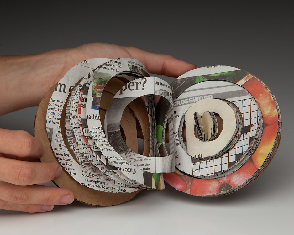 Cut newspaper bound into circular book structure and sewn with a coptic stitch
