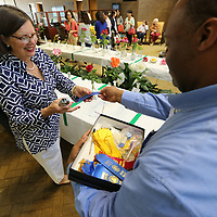 Tracy Kramer, left, and Kevin Ball begin placing ribbons on all the winners from Thursday's annual Rose Show held at the Renasant bank in downtown Tupelo.