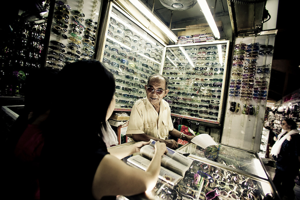 Sunglass salesman sporting cool shades in market, Saigon, Vietnam