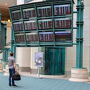 A lone passenger checks his flight information at Orlando International Airport on Friday, April 17, 2020 in Orlando, Florida. (Alex Menendez via AP)