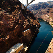 Photo of the bottom of the Hoover Dam complex feeding into the lower Colorado River. At bottom of the frame are the twin buildings housing the hydroelectric turbines. At top is the new Mike O'Callaghan – Pat Tillman Memorial Bridge which now handles much of the road traffic over the chasm.
