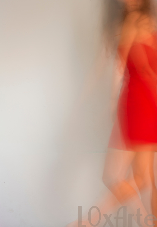 A free-spirited young woman wearing a red dress dances freely in front of a light background.  More images on the theme available on request.