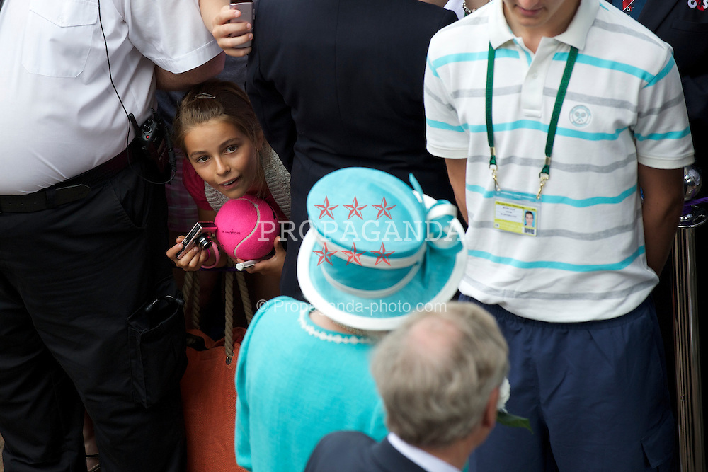 LONDON, ENGLAND - Thursday, June 24, 2010: A young spectator tries to get a picture of HRH Queen Elizabeth II (Elizabeth Alexandra Mary) as she visits on day four of the Wimbledon Lawn Tennis Championships at the All England Lawn Tennis and Croquet Club. (Pic by David Rawcliffe/Propaganda)