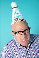 Portrait of angry senior man with shuttlecock on head over colored background