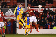 Preston striker Joe Garner  and Nottingham Forest defender Matt Mills (Capt) in the air during the Sky Bet Championship match between Nottingham Forest and Preston North End at the City Ground, Nottingham, England on 8 March 2016. Photo by Jon Hobley.