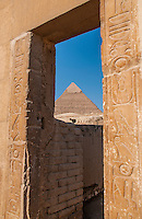 View of the Chephren pyramid through a doorway decorated with hieroglyphics.