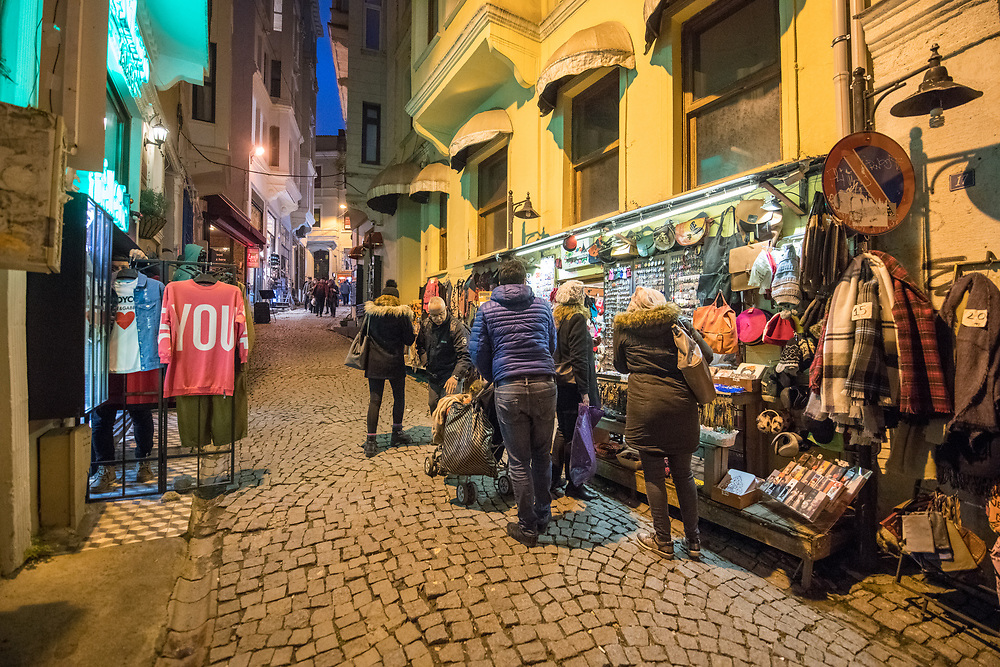 Shoppers browse through various accessories for sale in market stall on narrow cobblestone street in Istanbul, Turkey