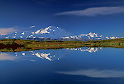 Denail and Alaska range Mountains and clouds refelcted in calm lake, blue sky, white clouds. Fall tundra colors.