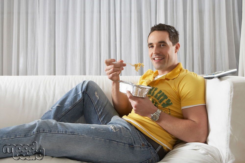 Young man sitting on sofa eating noodles from takeaway tray