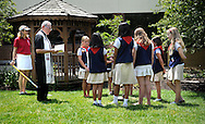 9 JUNE 2012 -- COTTLEVILLE, Mo. -- Monsignor James Callahan, pastor at St. Joseph - Cottleville,  joins members of American Heritage Girls Troop 1776 as they dedicate a tree on the church grounds during their year-ending meeting in Cottleville, Mo. Saturday, June 9, 2012. Mary Liddy (left), one of the troop leaders, prepares soil for the girls to add to the tree as part of the dedication ceremony. Photo © copyright 2012 Sid Hastings.