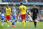 Brighton's Bruno Saltor talks to Watford Troy Deeney and Referee Keith Stroud walks past during the Sky Bet Championship match between Brighton and Hove Albion and Watford at the American Express Community Stadium, Brighton and Hove, England on 25 April 2015. Photo by Phil Duncan.