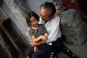 A typical Hutong (old style district). Man with granddaughter.