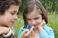 Brother and sister (7-9) examining caterpillar in field
