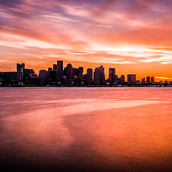 Boston skyline sunset with a beautiful colorful orange and purple sky. Scene includes downtown Boston city skyscrapers across Boston Harbor.