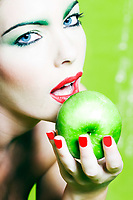 beautiful caucasian woman portrait hold an apple studio on green background