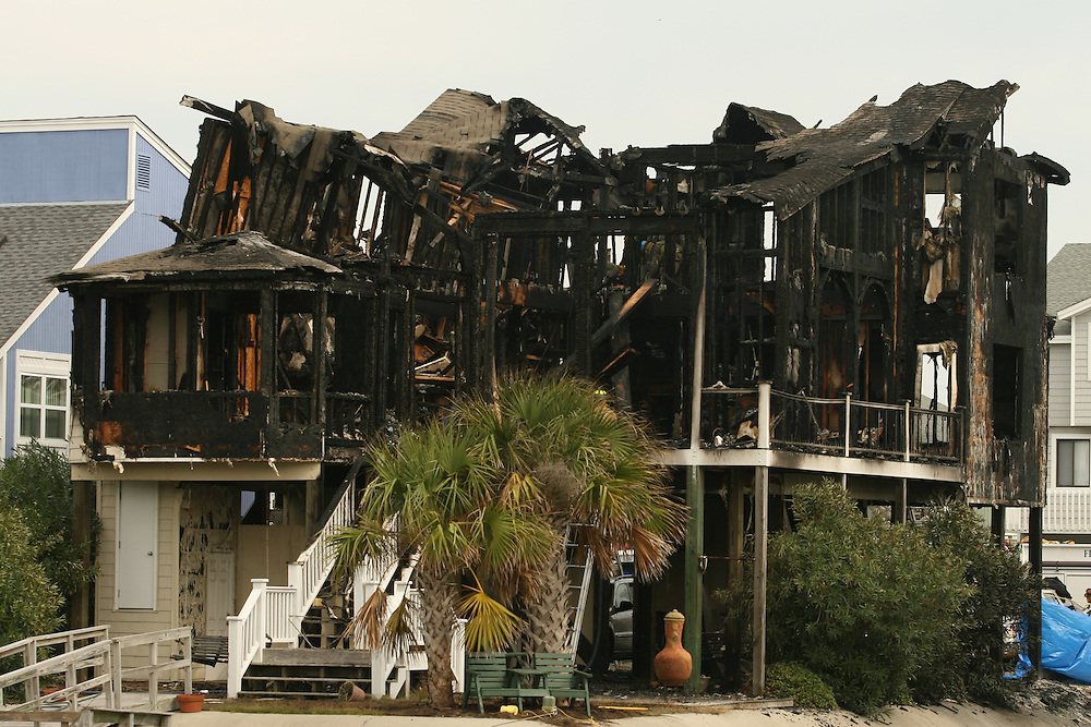 OCEAN ISLE, NC, OCTOBER 28: Firefighters and authorities search through the ruins of a house fire October 28, 2007 in Ocean Isle, North Carolina. The fire killed at least six people and sent another six to the hospital, another remains missing. According to reports, most of the people inside the house were students from the University of South Carolina. (Photo by Logan Mock-Bunting)