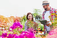 Portrait of mature gardener writing report on clipboard over flowers in shop with woman buyer