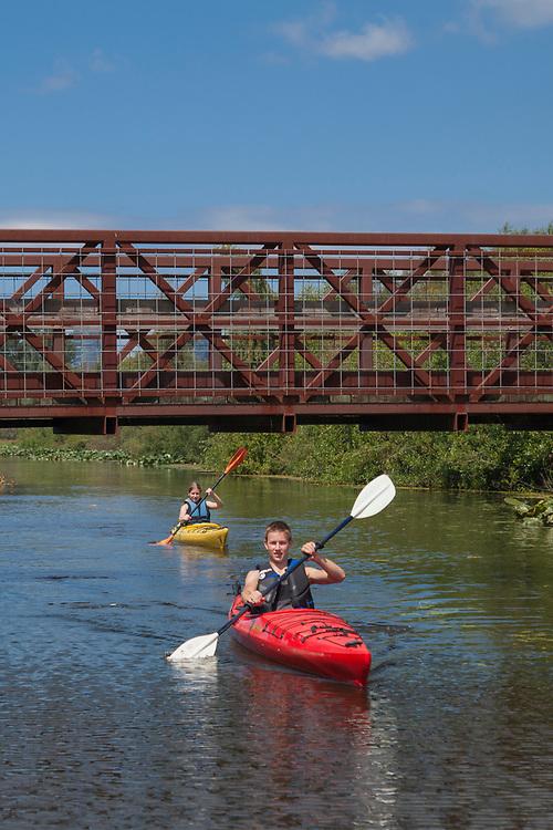 United States, Washington, Bellevue, teenage boy and girl kayaking under bridge in Mercer Slough Nature Park.  MR