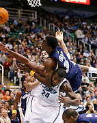 Memphis Grizzlies center Hasheem Thebeet (36) falls on top of Utah Jazz forward Paul Millsap (24) while trying to score as center Carlos Boozer (5) also defends during the first period of their NBA basketball game Monday  Nov. 30, 2009, in Salt Lake City. (AP Photo/Colin Braley)