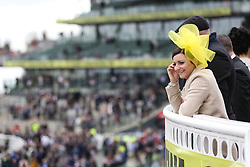 © Licensed to London News Pictures. 09/04/2016. Liverpool, UK. An elegant looking lady smiles as she looks over the racecourse on Grand National day of the Grand National 2016 at Aintree Racecourse near Liverpool. The race, which was first run in 1839, is the most valuable jump race in Europe. Photo credit : Ian Hinchliffe/LNP