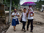 "22 JANUARY 2018 - GUINOBATAN, ALBAY, PHILIPPINES: Students in Guinobatan wear face masks while they walk home. Several communities in Guinobatan were hit ash falls from the eruptions of the Mayon volcano and many people wore face masks to protect themselves from the ash. There were a series of eruptions on the Mayon volcano near Legazpi Monday. The eruptions started Sunday night and continued through the day. At about midday the volcano sent a plume of ash and smoke towering over Camalig, the largest municipality near the volcano. The Philippine Institute of Volcanology and Seismology (PHIVOLCS) extended the six kilometer danger zone to eight kilometers and raised the alert level from three to four. This is the first time the alert level has been at four since 2009. A level four alert means a ""Hazardous Eruption is Imminent"" and there is ""intense unrest"" in the volcano. The Mayon volcano is the most active volcano in the Philippines. Sunday and Monday's eruptions caused ash falls in several communities but there were no known injuries.    PHOTO BY JACK KURTZ"
