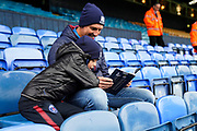 Southend United fans read the program during the EFL Sky Bet League 1 match between Southend United and Oxford United at Roots Hall, Southend, England on 6 October 2018.