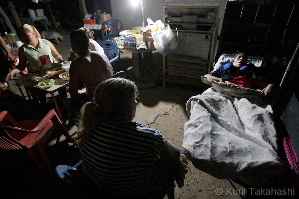 Mariana de la Torre, 29, sleeps while family members eat dinner at her house in Apatzingan, Mexico on Feb 26, 2009.<br /> (Photo by Kuni Takahashi)