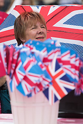 Trafalgar Square, London, June 12th 2016. Rain greets Londoners and visitors to the capital's Trafalgar Square as the Mayor hosts a Patron's Lunch in celebration of The Queen's 90th birthday. PICTURED: A woman's umbrella and a bucket of flags embody the patriotic nature of the day.